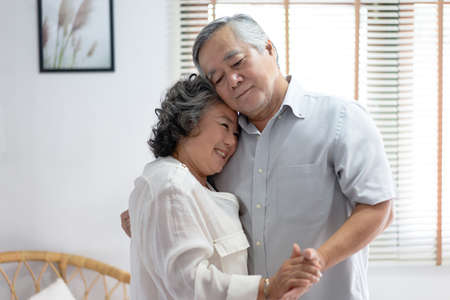 Lovers in a living room. Beautiful Asian senior couple smiling are enjoying spending time together while dancing. Senior family enjoying tender moment, celebrating anniversary. Imagens