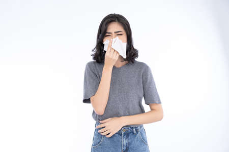 Portrait of young Asian woman blowing running nose got flu caught cold sneezing in tissue. Her sick allergic having allergy symptoms coughing holding napkin on isolated over white background.