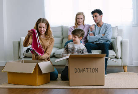 Teenage daughter and younger brother sit on the floor packing clothes into donation box at home. Happy volunteer family separating donations clothes in carton package donate to needy people, reuse. Imagens