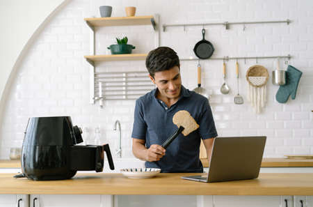 Portrait of handsome man cooking bread with air fryer while having video conference call via computer in kitchen at home. Male stay at home and work from home.  New normal lifestyle concept.