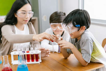 Cute Asian elementary schoolboy doing science while classmates looking his in science class with young Asian teacher. Child and science. Education concept. Imagens