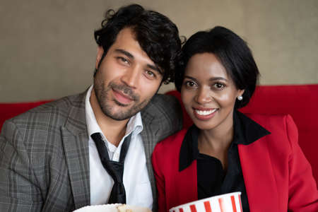 Happy african mixed race ethnicity couple look at camera relaxing on couch at cinema. American spouses sit on couch spend weekend with popcorn and romantic movie concept.