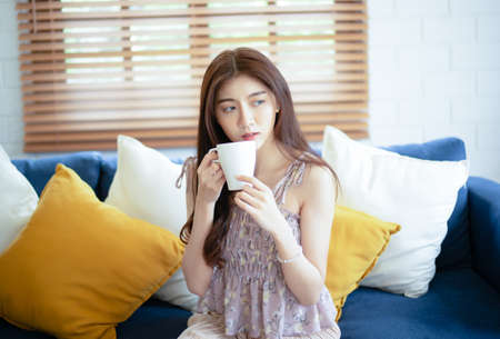 Beautiful young Asian woman relaxing drinking cup of hot coffee or tea and looking away while sitting on couch at home in the living room. People relax and lifestyle concept.