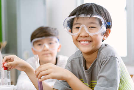 Portrait of little scientist Asian boy in safety glasses smiling at the camera while examining a test tube in science class. Elementary School Science Classroom. Children Learn with Interest. Imagens