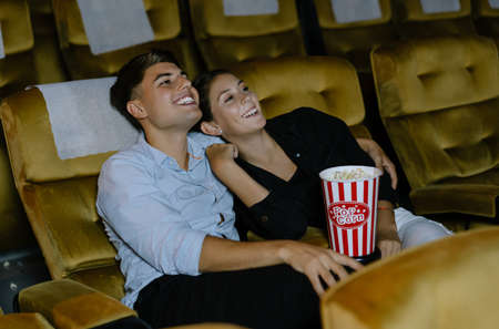 Happy loving young couple with popcorn enjoying a comedy movie together at the cinema. Loving couple spend weekend free time together. Imagens