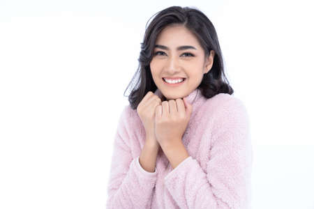 Portrait of young beautiful Asian woman smiling friendly wearing pink winter knitted and looking at camera against isolated white background. Concept woman lifestyle and winter. Autumn, winter season. Imagens