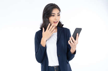 Portrait of a shocked surprised Asian business woman looking at phone seeing good news or photos with emotion on her face isolated on white background. Human emotion, reaction, expression.