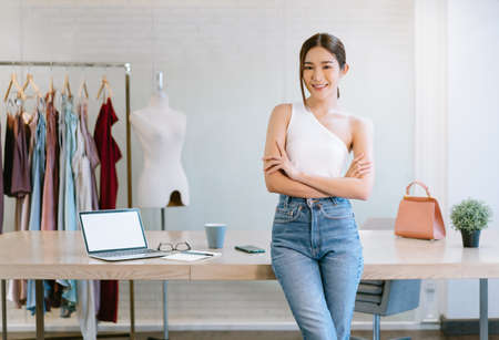 Portrait of beautiful young Asian woman fashion designer working small business owner standing with arms crossed in luxury workshop studio. Start up small business owner entrepreneur SME Concept. Imagens