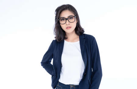 Portrait of a young beautiful Asian girl wearing eyeglasses posing while standing and looking at camera isolated over white background.  Concept of business woman. Imagens
