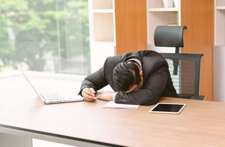 Portrait of tired and sleepy Asian businessman in office desk. He worked and fell asleep on the desk.  Stress at work and Lack of motivation concept.