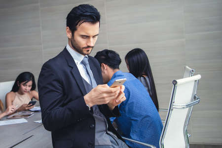 Handsome businessman standing using mobile phone while taking a break during a conference room meeting with a colleague multi-ethnic. Work break concept Imagens