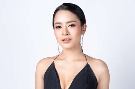 Glamour portrait of beautiful Asian woman in Sexy Black Dress with tassel earrings silver and looking at camera. Fashion shiny highlighter on skin and sexy gloss lips, perfect make-up.