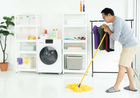 Asian man wearing grey sweater washing floor with mopping stick and bucket in laundry room of bright modern apartment. Housekeeper, everyday life, Routine concept.