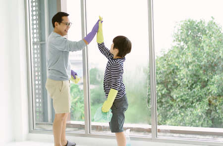 Happy Asian Father and son giving each other high-five after cleaning wiping window finished. Well done, give me five, doing everything together, trust, House-keeping service concept. Imagens