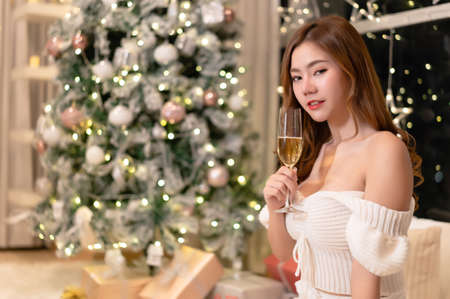 Portrait of beautiful young korean girl drinking champagne and looking at camera in decorated room with christmas tree at home.