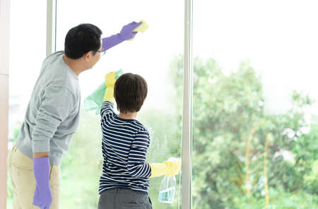 Asian Family Cleaning Day. Happy Dad and son cleaning window together on Holidays. Family housework and household concept.