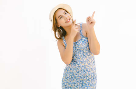 Beautiful young Asian woman dressed in blue floral dress and wearing summer straw hat  pointing fingers up with two hands at copy space isolated over white background.