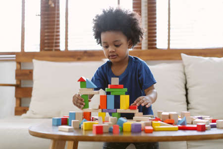 Little African american boy building a small house with colorful wooden blocks in living room at home. Educational toys for preschool and kindergarten children. Imagens