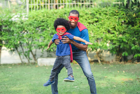 African black family spent time together in the home garden. Laughing father and son playing superhero at the day time. Happy African American family life, Father Day concept