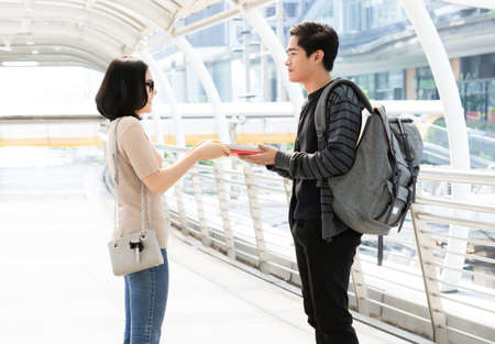 Portrait fo a cheerful young Asian couple exchanging different books on the city. Person borrow textbook, swap of knowledge. Give to read to a boyfriend.