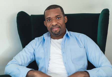 Portrait of middle age smiling African american and looking at camera while sitting on green sofa in living room at home.