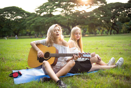 Two young beautiful blond smiling hipster girls sitting on the grass leaning against each other back on park enjoy nice day. Two young girl friends having fun play the guitar and sing songs. Foto de archivo
