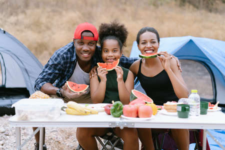 Portrait of african american family having fruit and snack outside the tent at campsite and looking at camera. Holiday Family activity outdoor concept. Foto de archivo