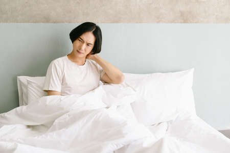 Unhappy young Asian man waking up in uncomfortable bed feeling neck ache after sleep on bad mattress in incorrect posture, sleeping on uncomfortable pillow at home. Healthcare Concept