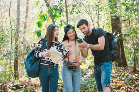 Three friends tourist with maps and using map on smartphone for searching direction and find way out, backpack traveling for freedom lifestyle on vacation. Tourism and Friendship Concept