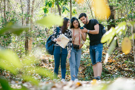 Group of Young Smiling People traveler using mobile phone for GPS map searching direction in nature forest. Three friends travel backpack for freedom lifestyle on vacation.Tourism, Friendship Concept Foto de archivo