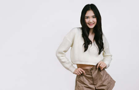 Beautiful young Asian woman in brown shorts and white sweater standing smiling looking camera on isolated over white background with copy space. Foto de archivo