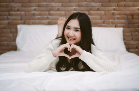 Happy young Korean girl  lying at the end of the bed shows gesture heart with fingers and looking at camera. Portrait of smiling lady posing in bright home apartments. Concept happiness and love.
