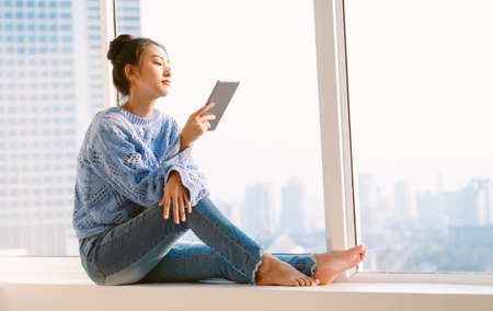 Beautiful young Asian woman in warm knitted sweater and using tablet computer while sitting on a window sill at home. Lifestyle, comfort and technology concept. Fashion, Autumn, winter.