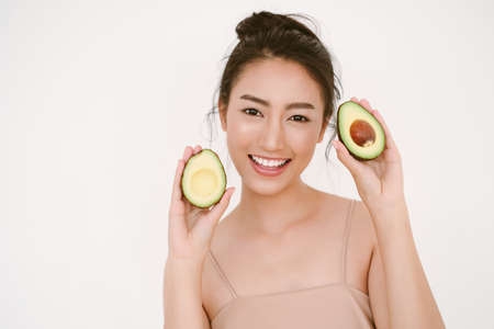 Beautiful young Asian woman with healthy glow perfect smooth skin and holding avocado in hands near the face isolated on white background. Skin care, beauty Natural, Healthy Lifestyle, Health Concept.