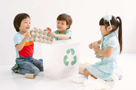 Group of multiethnic preschool children learning about recycling,waste separation in classroom, teaching in teamwork. Recycling and Ecology protection concept.