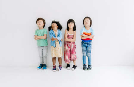 Ethnicity Diversity Group of kids with crossed arms looking up over gray background. Childhood, freedom, happiness, active lifestyle concept.