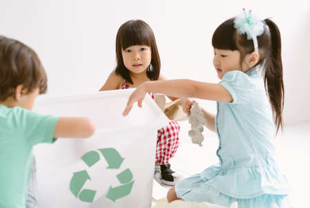 Group of adorable kids school kindergarten learning biology recycle environment, sort waste in classroom at kindergarten. Education, Recycling and Ecology protection concept. Foto de archivo