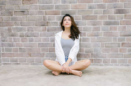 Portrait of young Korean woman sitting on the floor and looking up at the brick wall Background. Beautiful Asian woman healthy and beauty lifestyle girl Concept. Foto de archivo
