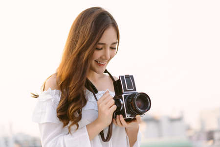 Beautiful young Asian stylish woman taking photos with retro film camera on the rooftop of a building. Asian girl smiling enjoy weekends, Holiday lifestyle trip. Foto de archivo