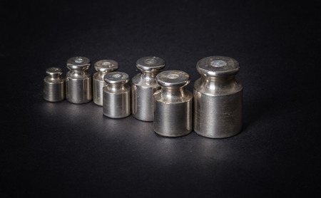 a set of small metal weights on a gray background