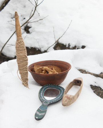 sacral: Spindle, mirror and clay plate with bread in the snow. Pagan altar, offering of gifts. Still life.