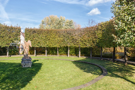 Old antique angel statue on a green lawn surrounded by trimmed linden trees Stockfoto