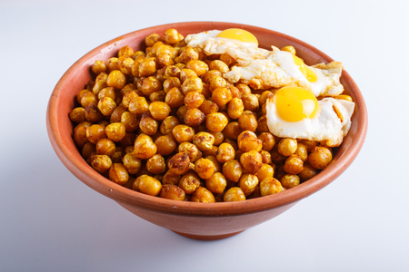 Fried chickpeas with quail eggs and spices in a clay plate isolated on white background, close up.