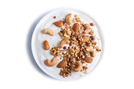 White plate with greek yogurt granola, almond, cashew, walnuts isolated on white