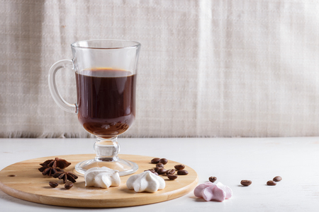 Glass cup of coffee with meringues on a wooden board on a white background. close up, copy space.