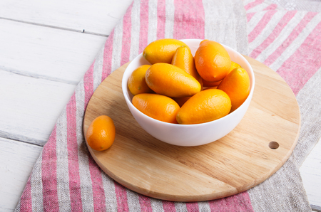 kumquats in a white plate on a white wooden background, close up.