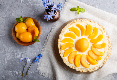 Round peach cheesecake and ceramic vase with blue flowers on a linen napkin on a gray concrete background. top view, close up. Stock Photo