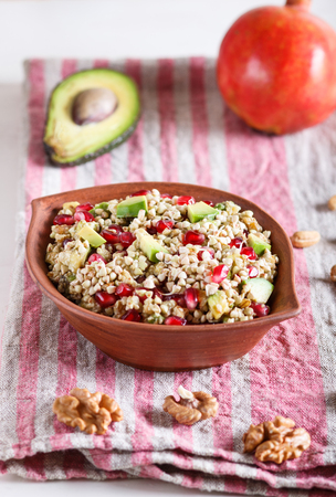 Salad of germinated buckwheat, avocado, walnut and pomegranate seeds in clay plate on white wooden background. Side view, close up, selective focus. Foto de archivo