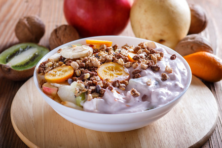 Vegetarian salad of bananas, apples, pears, kumquats, kiwi with granola and yogurt