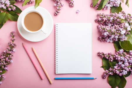 Purple lilac flowers and a cup of coffee  with notebook and colored pencils on pastel pink Reklamní fotografie - 124156265
